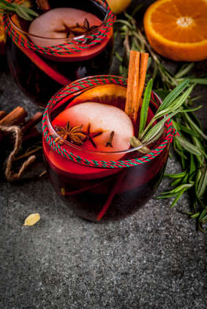 Traditional winter and autumn drinks. Christmas and Thanksgiving Cocktails. Mulled wine with orange, apple, rosemary, cinnamon and spices on a dark stone background, copy space Stock Photo