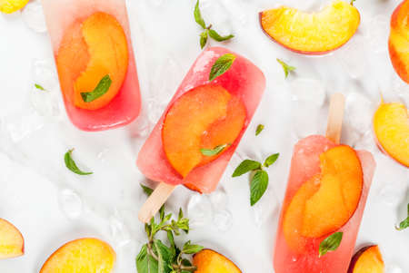 Summer desserts. Frozen drinks. Sweet fruit ice cream from frozen peach tea with mint. On a white marble table, with ingredients - peaches, mint, ice. Copy space