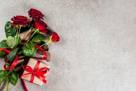 Holiday  background, Valentines day. Bouquet of red roses, tie with a red ribbon, with wrapped gift box and red candle. On a gray stone table, copy space top view Banque d'images