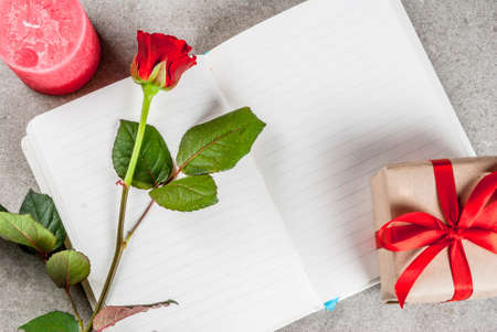 Holiday  background, Valentines day. Bouquet of red roses, tie with a red ribbon, with blank notepad, wrapped gift box and red candle. On a gray stone table, copy space top view Banque d'images