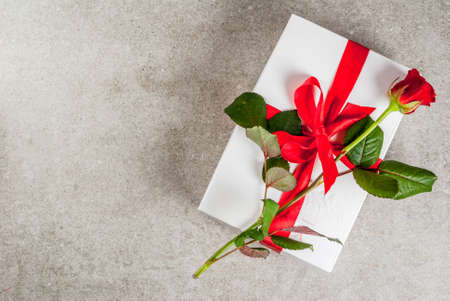 Holiday  background, Valentines day. Wrapped gift box with one red rose. On a gray stone table, copy space top view Banque d'images