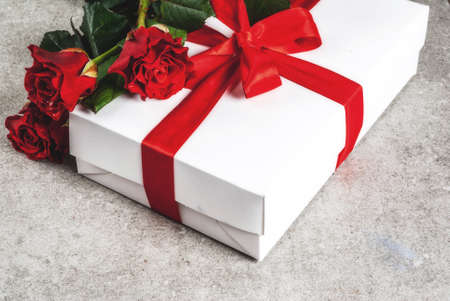 Holiday  background, Valentines day. Bouquet of red roses, tie with a red ribbon, with wrapped gift box. On a gray stone table, copy space