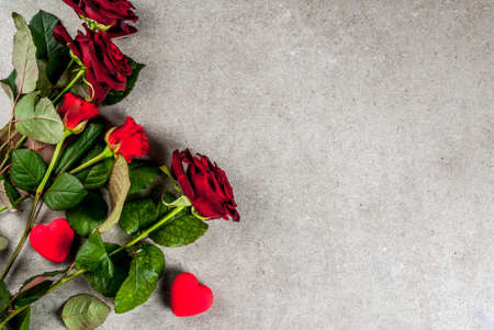 Holiday  background, Valentines day. Bouquet of red roses, tie with a red ribbon, with wrapped gift box. On a gray stone table, copy space top view Banque d'images
