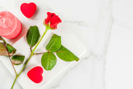 Holiday  background, Valentines day. Bouquet of red roses, tie with a red ribbon, with blank notepad, wrapped gift box and red candle. On a white marble table, copy space top view
