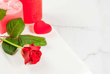 Holiday  background, Valentines day. Bouquet of red roses, tie with a red ribbon, with blank notepad, wrapped gift box and red candle. On a white marble table, copy space