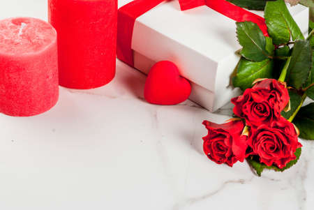 Holiday  background, Valentines day. Bouquet of red roses, tie with a red ribbon, with wrapped gift box. On white marble table, copy space Banque d'images