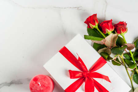 Holiday  background, Valentines day. Bouquet of red roses, tie with a red ribbon, with wrapped gift box. On white marble table, copy space top view Banque d'images
