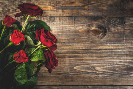 Holiday  background, Valentines day. Bouquet of red roses, tie with a red ribbon. On a wooden table, top view copy space