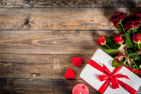 Holiday  background, Valentines day. Bouquet of red roses, tie with a red ribbon, with wrapped gift box. On wooden table, copy space top view