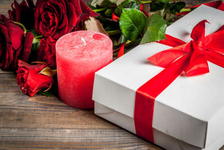 Holiday  background, Valentines day. Bouquet of red roses, tie with a red ribbon, with wrapped gift box. On wooden table, copy space