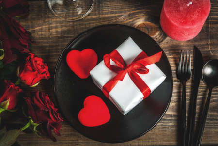 Table setting for Valentines day. Bouquet of red roses, tie with a red ribbon, gift box, red hearts, candle, plate, fork, spoon and knife. On a wooden table, top view copy space Banque d'images