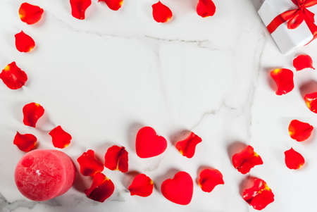 Valentines day background with rose flower petals, white wrapped gift box with red ribbon and holiday red candle, on white marble background, copy space top view frame Stock Photo