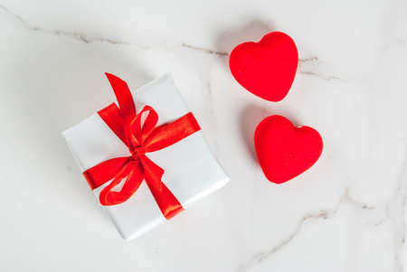 Valentines day concept, white wrapped gift box with red ribbon and red velvet hearts, on white marble background, copy space top view