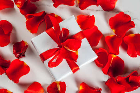 Valentines day concept, with rose flower petals and white wrapped gift box with red ribbon, on white marble background, copy space top view