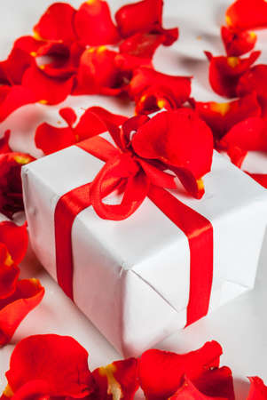 Valentines day concept, with rose flower petals and white wrapped gift box with red ribbon, on white marble background, copy space