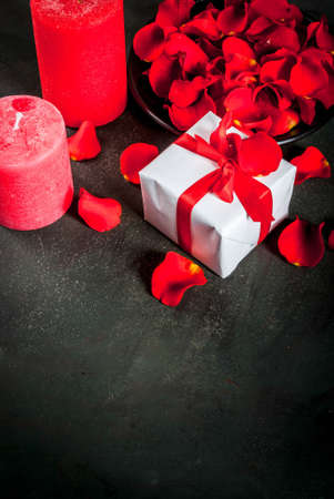 Valentines day background with rose flower petals, white wrapped gift box with red ribbon and holiday red candle, on dark stone background, copy space