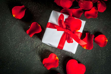 Valentines day background with rose flower petals, white wrapped gift box with red ribbon and holiday red candle, on dark stone background, copy space top view