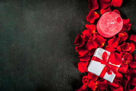 Valentines day concept, with rose flower petals and white wrapped gift box with red ribbon, on dark stone background, copy space top view Banque d'images