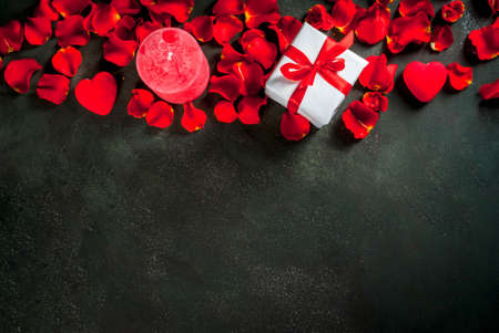 Valentines day concept, with rose flower petals and white wrapped gift box with red ribbon, on dark stone background, copy space top view Stock Photo