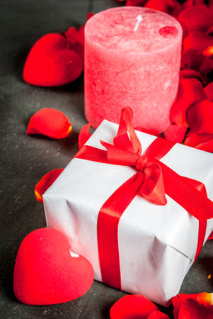 Valentines day concept, with rose flower petals and white wrapped gift box with red ribbon, on dark stone background, copy space