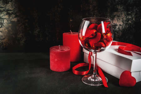 Valentines day concept, white wrapped gift box with red ribbon, rose flower petals in wine glass, with red candle, on dark stone background, copy space Stock Photo