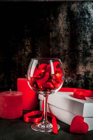 Valentines day concept, white wrapped gift box with red ribbon, rose flower petals in wine glass, with red candle, on dark stone background, copy space Banque d'images