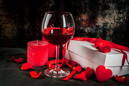 Valentines day concept, white wrapped gift box with red ribbon, rose flower petals, red wine glass, with red candle, on dark stone background, copy space