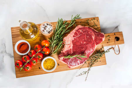 Fresh raw meat, lamb beef marble steak on a cutting board, with ingredients for cooking. On white marble table, copy space top view