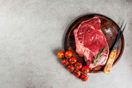 Fresh raw meat, lamb beef marble steak on a cutting board, with ingredients for cooking. On grey stone table, copy space top view Stock Photo - 91286111