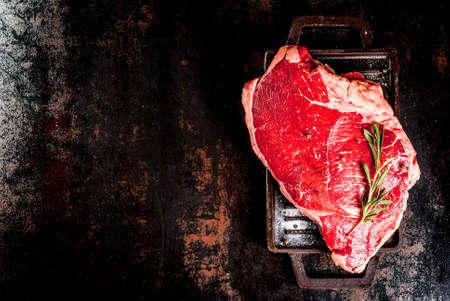 Viande crue fraîche, steak de marbre de b?uf d'agneau sur une plaque de cuisson grill, avec les ingrédients pour la cuisson. Sur la table en métal rouillé foncé, copie vue de dessus de l'espace Banque d'images - 91286098