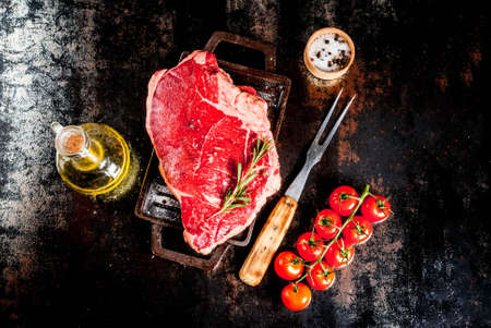 Fresh raw meat, lamb beef marble steak on a grill pan board, with ingredients for cooking. On dark rusty metal table, copy space top view Banque d'images
