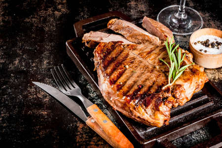 Grilled beef steak with spices on grill pan board, with and red wine glass. Copy space