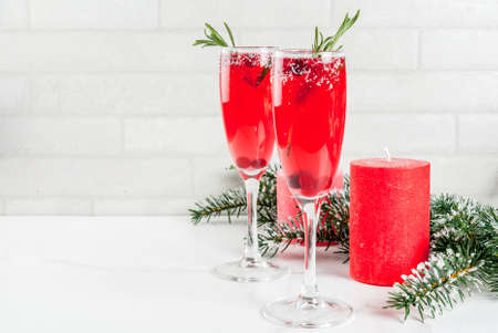 Christmas morning red cranberry mimosa with rosemary, white marble background copy space with christmas decorations