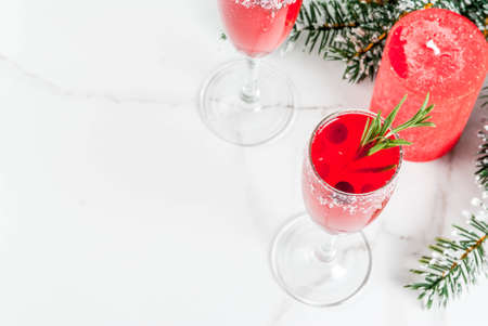 Christmas morning red cranberry mimosa with rosemary, white marble background copy space with christmas decorations top view Stock Photo