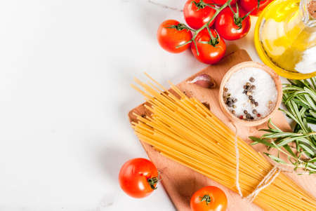 Italian food cooking, ingredients for preparation pasta spaghetti - tomato, garlic, olive oil, spices, white marble background, copy space top view