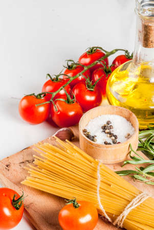 Italian food cooking, ingredients for preparation pasta spaghetti - tomato, garlic, olive oil, spices, white marble background, copy space Stockfoto