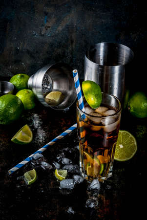 Cuba Libre, long island or iced tea cocktail with strong alcohol, cola, lime and ice, two glass, dark background copy space Stockfoto