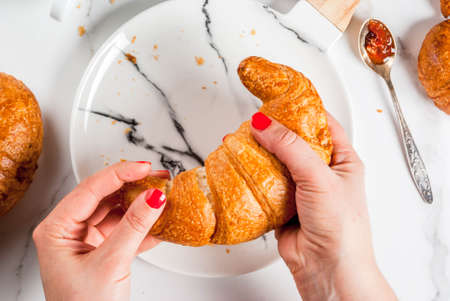 Girl eats homemade continental breakfast, croissants, coffee. jam on white marble table, copy space top view, hands in picture