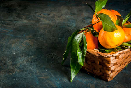 Fresh raw organic Tangerines with green leaves in little basket on dark concrete stone background, copy space Stockfoto