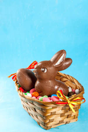 Chocolate easter eggs, bunny and sweets in the basket on light blue background, easter concept, copy space Stockfoto