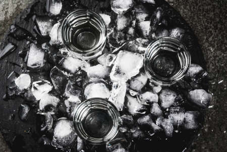 Alcohol and cocktails. Three glasses of vodka on a slate tray, with ice. On a black stone table, Copy space top view Stockfoto