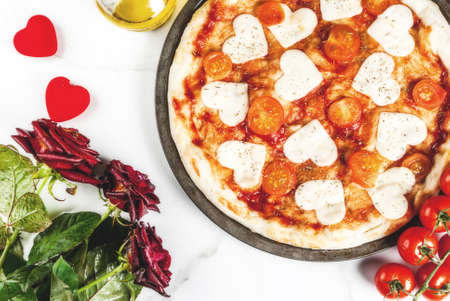 Valentine holiday food concept, pizza margarita with heart shaped cheese, white marble background, copy space top view, with roses Stockfoto