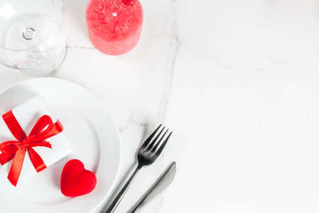 Valentines day table setting with plate, fork, knife, gift box and red heart, on white marble background top view copy space