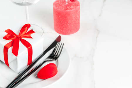 Valentines day table setting with plate, fork, knife, gift box and red heart, on white marble background copy space