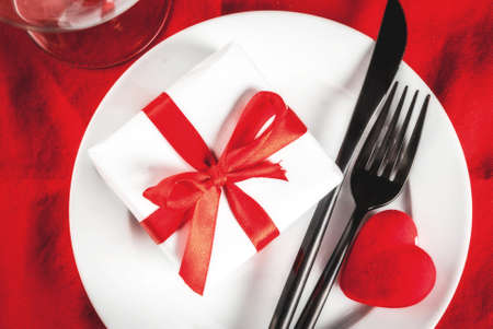 Valentines day table setting with plate, fork, knife, gift box and red heart, on red tablecloth background top view copy space