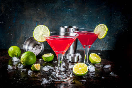 Red cosmopolitan cocktail with lime in martini glass, on dark rusty background copy space Archivio Fotografico