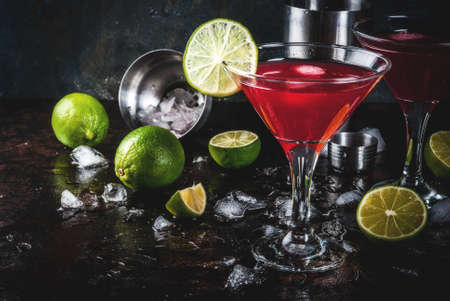 Red cosmopolitan cocktail with lime in martini glass, on dark rusty background copy space Фото со стока