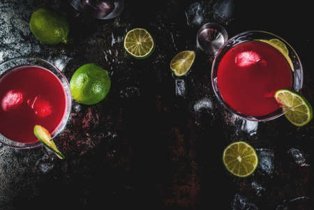 Cocktail cosmopolite rouge avec de la chaux dans un verre à martini, sur la vue de dessus de l'espace de copie fond rouillé sombre Banque d'images - 91497311