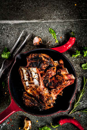 Raw fresh meat, roasted or grilled lamb or beef ribs with red tomato sauce, hot pepper, garlic and spices in skillet on dark stone background, copy space top view