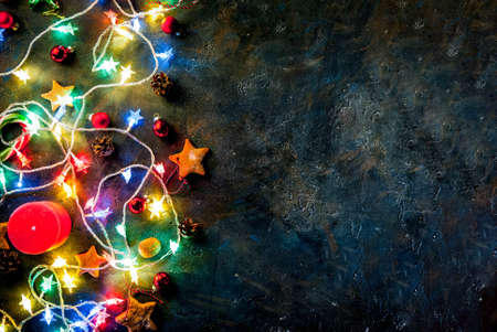 Christmas dark blue background with christmas garland, decorations, gingerbread stars  and candles.  Top view copy space